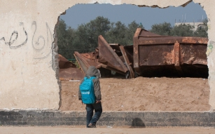 Boy looking at destroyed wall
