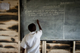Boy writes on classroom chalkboard