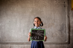 Faimonissa, 10, shows off her maths slate during an Activity Based Learning class, India.  Photo: Paloma Basi