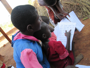 Teacher gives individualized attention to students practicing reading.  Photo Credit: Millennium Villages Project Staff.