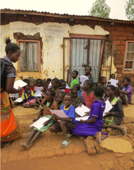 """In this photo, around 40 children are gathering at an MVP village learning center in southern Malawi. This was the only space available to hold the class after school hours. They range from first graders to 15 year olds who are still in grade 5.  Most are registered in school but remain illiterate in Chichewa – one of the local languages - and in English.  These projects are run by volunteers. The reading activities appear """"traditional"""", but are in fact quite innovative.  Photo Credit: Millennium Villages Project Staff."""