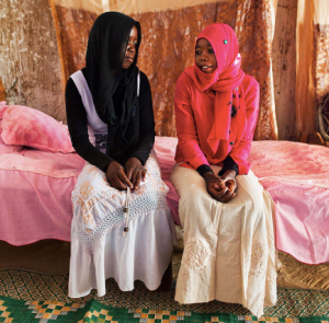 Sisters Nana and Zakia sit on a bed together. Nana married when she was only 13 years old, and had to stop going to school. Zakia married when she was only 17 years old. Her family arranged the marriage, but she never saw her husband until she got divorced due to the threats of her husband's second wife, currently living in Khartoum with him. Photo by Albert González Farran - UNAMID