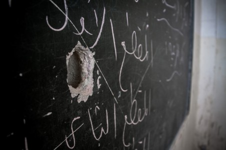 A bullet-hole scars the blackboard at the local school after armed groups occupied the school in Northern Syria.