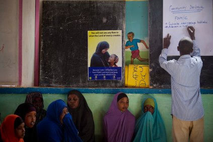 Women sit in a community meeting, organised by UNICEF, to raise awareness about the dangers of FGM while a community mobiliser writes on the notice board n the Shabelle IDP settlement in Garowe, Somalia Tuesday, July 1, 2014. (Kate Holt/ UNICEF Photo/)